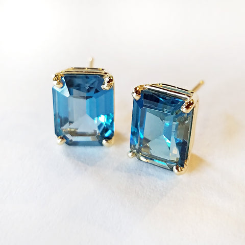 Emerald cut blue topaz shimmers like the Caribbean sea and is set in custom made gold stud earrings.