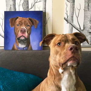 Brown pit bull dog sits on couch next to his portrait painting
