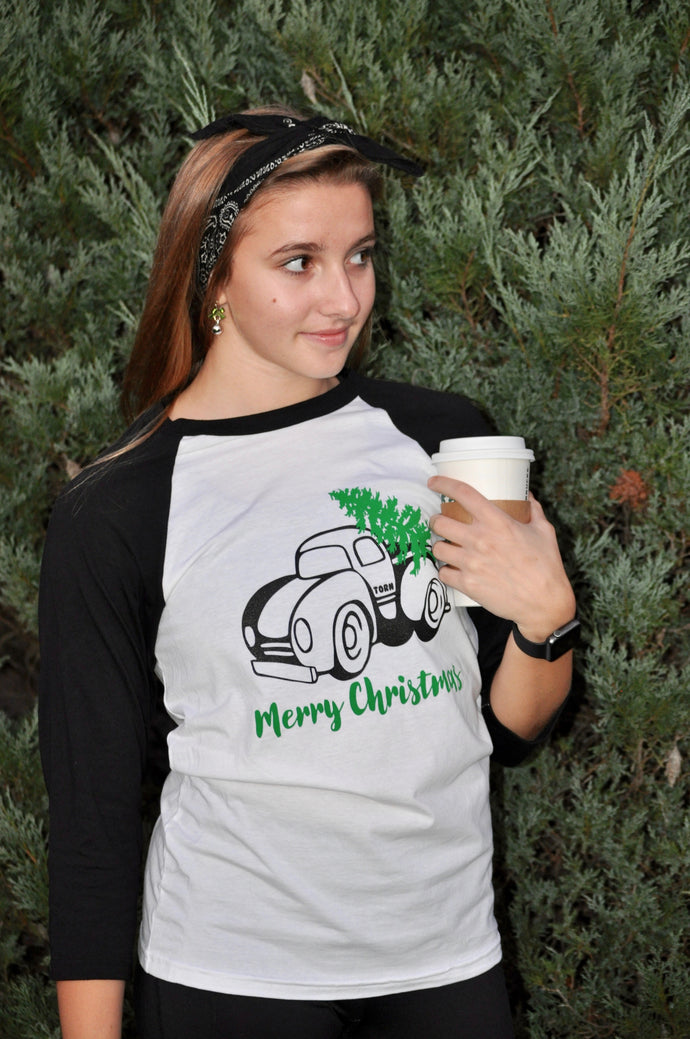 white shirt with black 3/4 length sleeves. Black old fashion truck with Green cursive merry Christmas written underneath and green Christmas tree in trunk of truck.