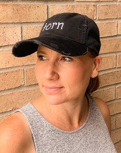 Black distressed hat with the word 'torn' embroidered on front.