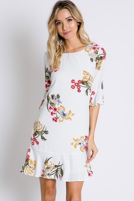 Off white shift dress with floral pattern. Ruffle at bottom of dress as well of the end of the 3/4 length sleeve.