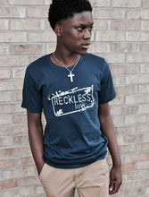 "Load image into Gallery viewer, navy shirt with ""reckless love"" printed on the front with grey ink. Rectangle decorative design around outside of words."