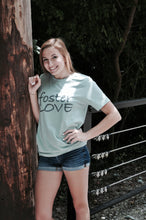 Load image into Gallery viewer, Dusty blue unisex tshirt with 'foster love' printed on the front in grey ink.
