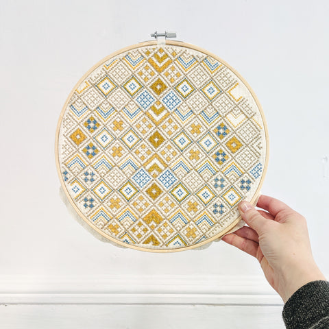 "Completed cross stitch hoop 10"" Geometric design by Futska. Stitched by Lucy Engels in Aurifil Thread."