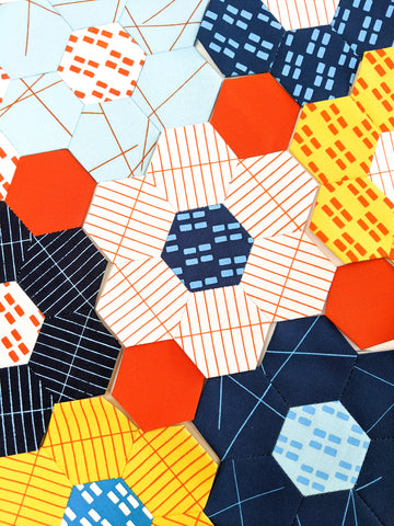 Close up hexagon english paper piecing using handprinted big summer 21 fabric bundle from Lucy Engels