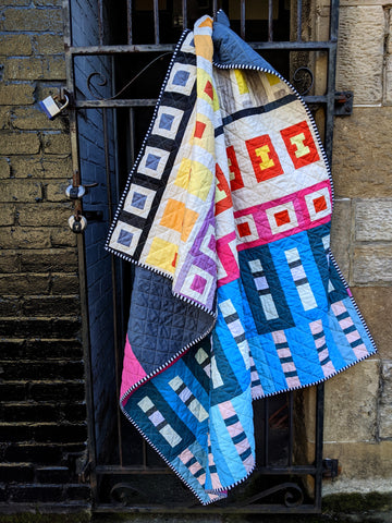 Go Quilt by lucy engels sew along quilt, brightly coloured quilt hanging on a gate