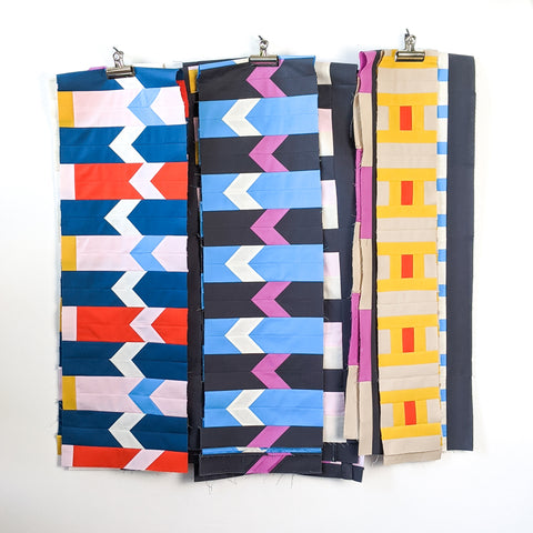 Now quilt rows hanging on a white wall - lucy engels