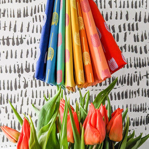 rainbow coloured fabric bundle with handprinted tulips hanging above a bunch of red peach real tulips