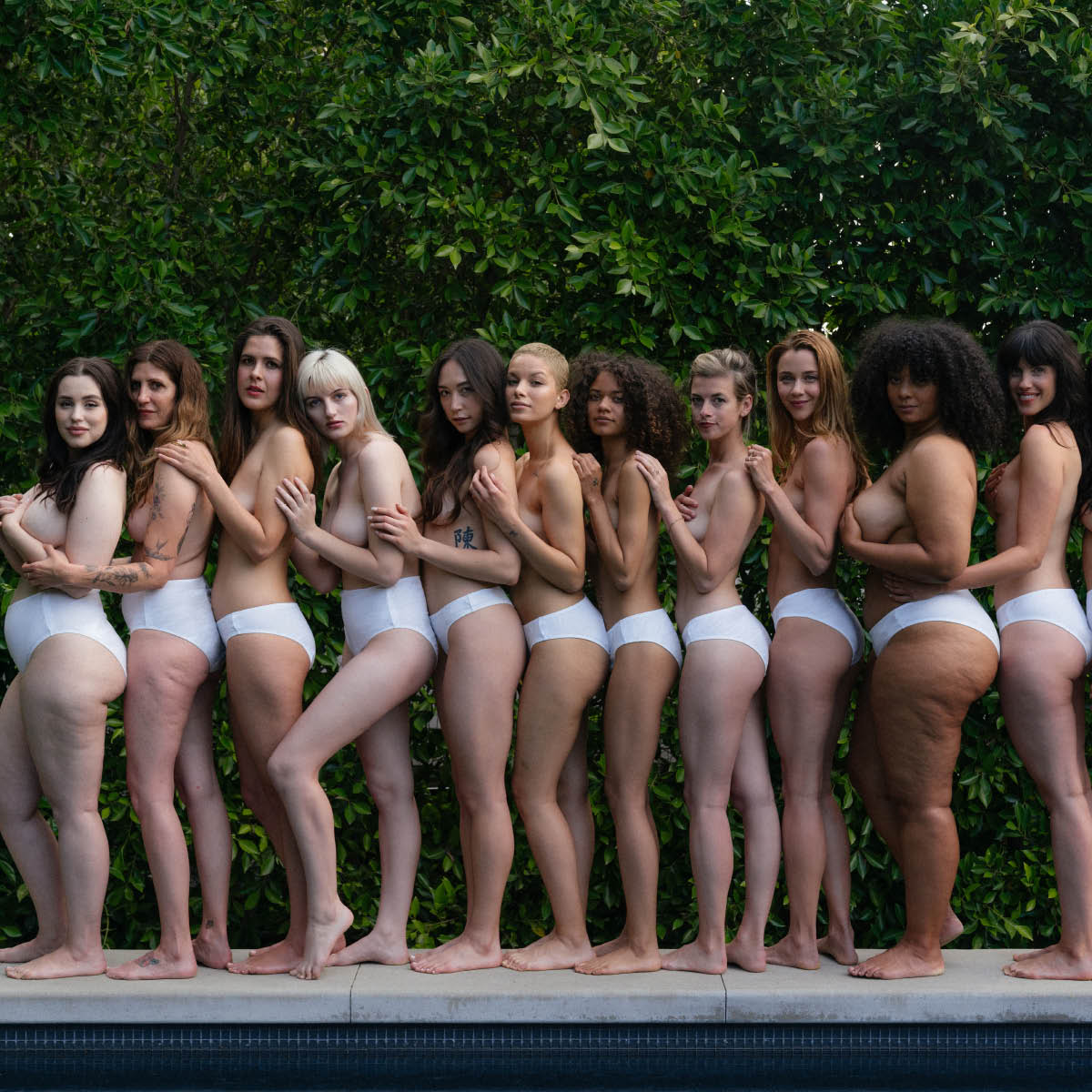 eleven women of different body types and ethnicities all wearing white organic cotton underwear, some wearing high-waist style underwear, some wearing organic cotton bikini underwear and some wearing organic cotton thong underwear outside.