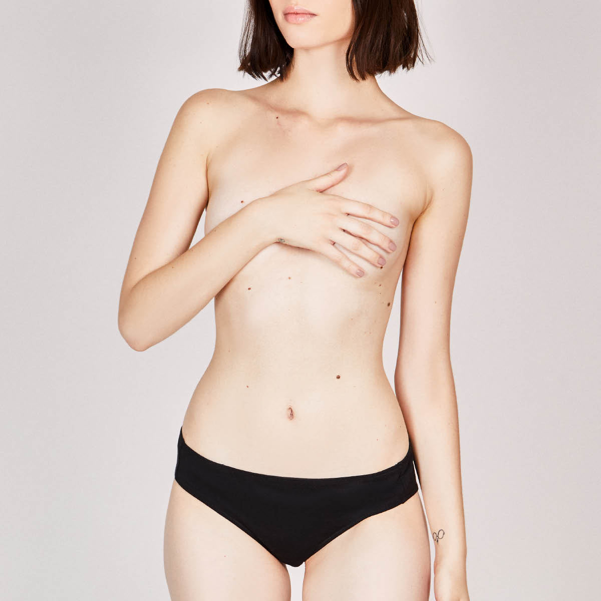 Woman wearing an organic cotton thong in black, low waist.