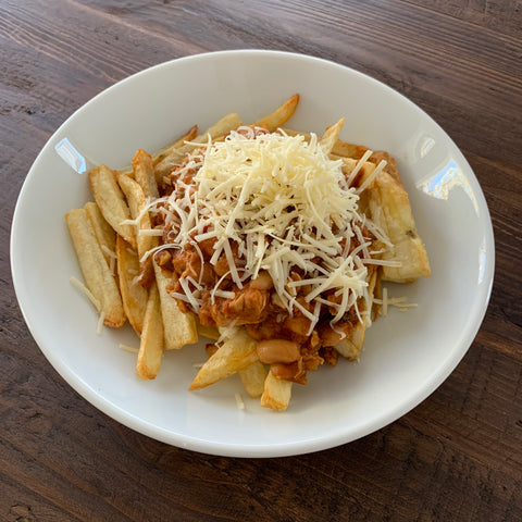 bowl of chicken chili over french fries with cheddar cheese on top over a wooden table