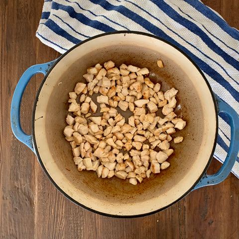 browned chicken pieces in a blue Dutch oven on top of a wooden table with a blue stripped towel in the corner