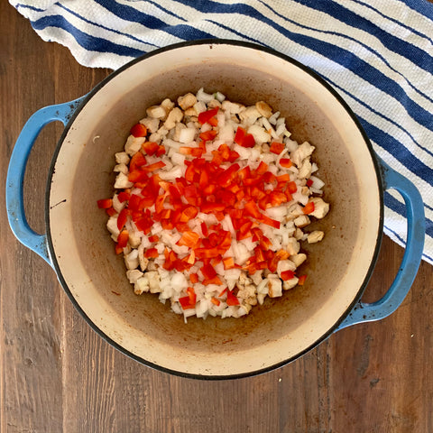 Blue Dutch oven pot on a wooden table filled with brown chicken and topped with chopped onions and red bell pepper. There is blue stripped towel in the corner.