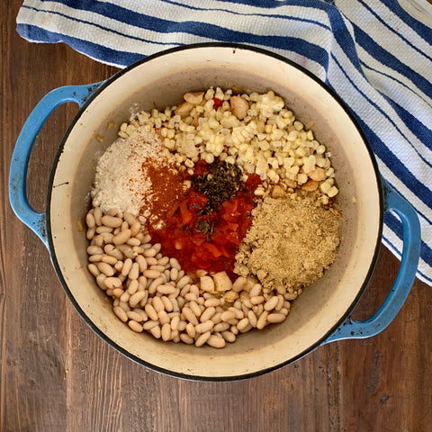 Blue Dutch oven with white beans, corn, spices, and tomatoes to make chicken chili on a wooden table