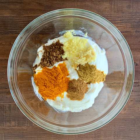 Spices in a bowl of yogurt for chicken tikka masala recipe