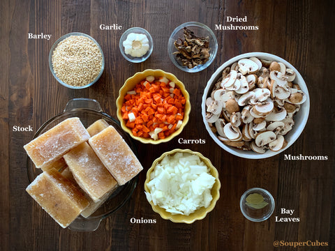 ingredients for mushroom barley soup in various bowls on a dark wooden table