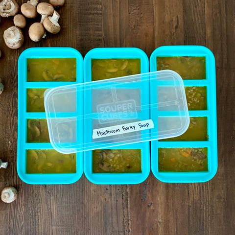 """image of 3 1-cup souper cubes trays filled with mushroom barley soup. there is a souper cubes lid on the top of one of the trays with a piece of masking tape that says """"mushroom barley soup"""""""