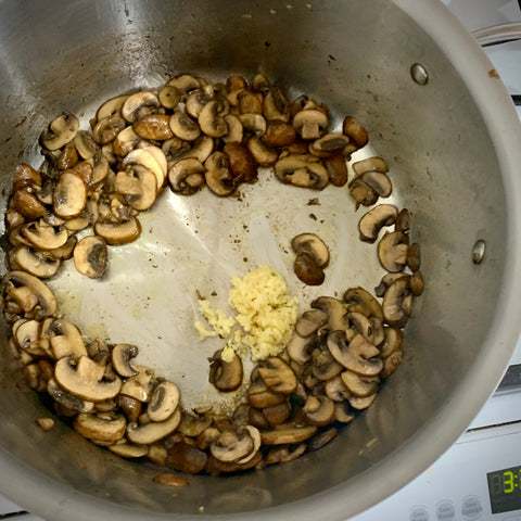 sauteed brown mushrooms with 4 cloves of minced garlic in a large all-clad pot for mushroom barley soup