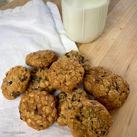 baked oatmeal cookies next to a cup of milk