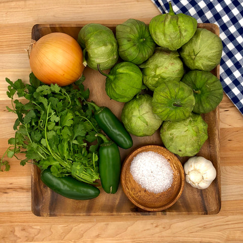 ingredients to make salsa verde on a wooden plate. includes: tomatillos, onion, cilantro, jalapeno, garlic, salt