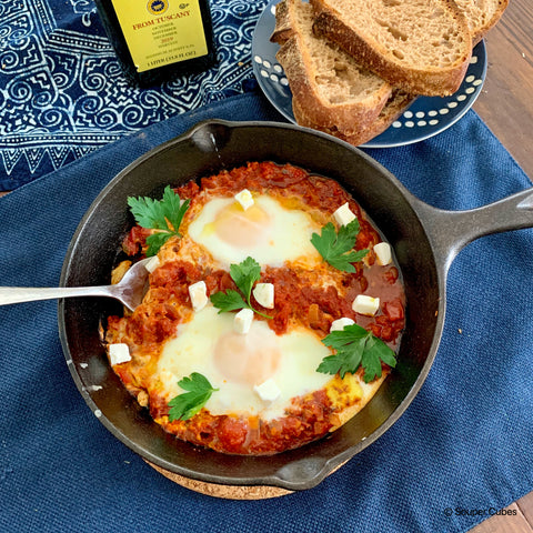image of cooked shakshuka in a cast iron pan with 2 eggs, feta cheese, and parsley