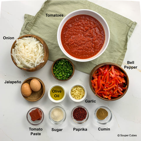 overhead shot of ingredients for shakshuka, including: tomatoes, onion, jalapeno, eggs, bell pepper, cumin, olive oil, garlic, tomato paste, sugar, and paprika