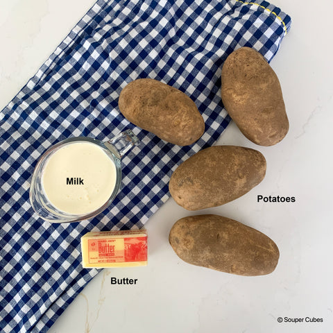 overhead shot of the ingredients for mashed potatoes: potatoes, milk, and butter
