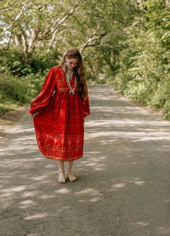 Photograph of a model in a rural setting wearing a 1970s style bohemian red midi dress with balloon sleeves.