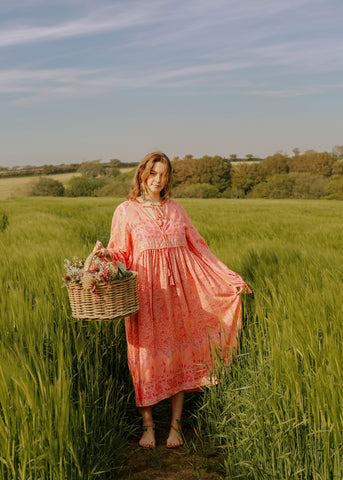Photograph of a model in a field wearing a long bohemian style pink midi dress with big balloon sleeves holding a straw basket.