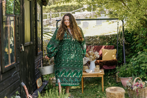 Photograph of a model in a bohemian setting wearing a 1970s style midi dress with exaggerated bishop sleeves in forest green colour.
