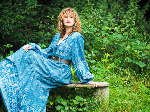 photograph of model wearing blue 1970s style bohemian dress with big balloon sleeves and long tiered flowy maxi skirt