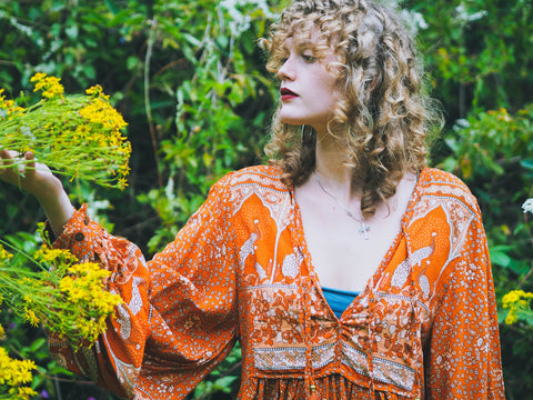 Photograph of a model wearing a 1970s style orange v neck top with balloon sleeves and ornate peacock print.