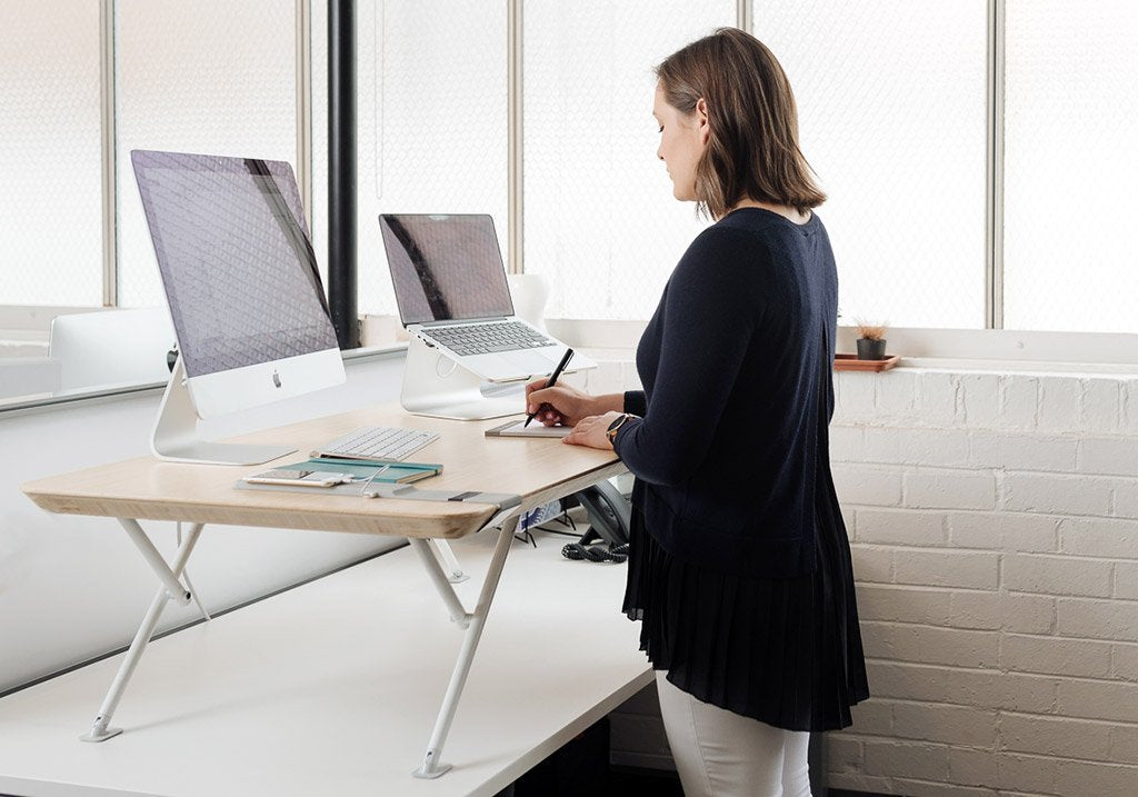 White | woman using standing desk
