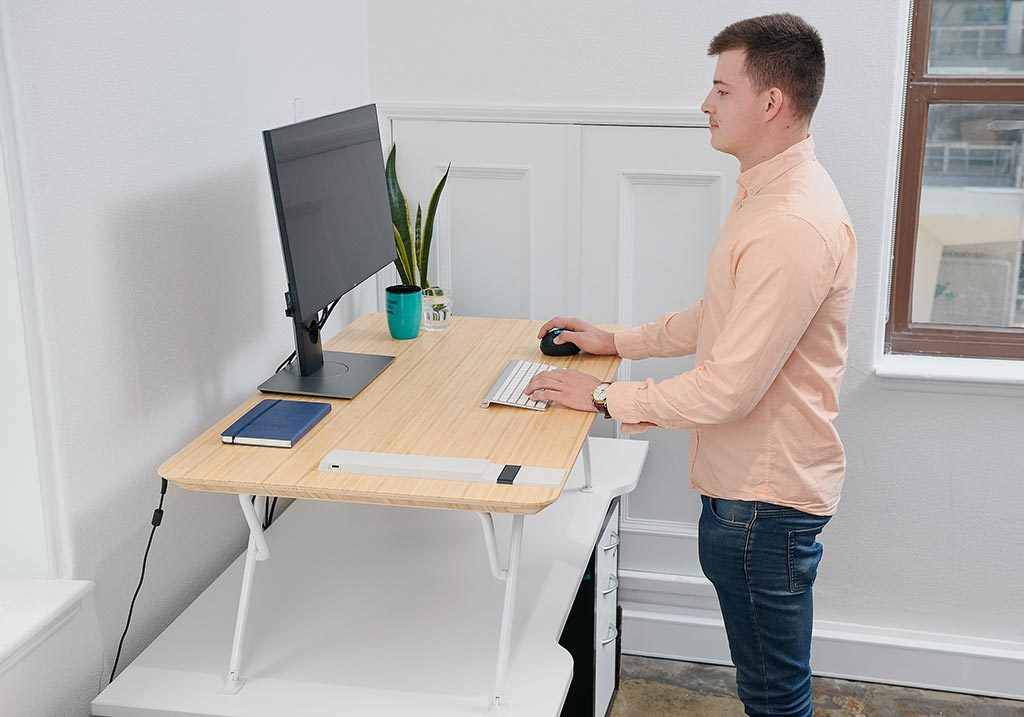 White | man using monitor on standing desk