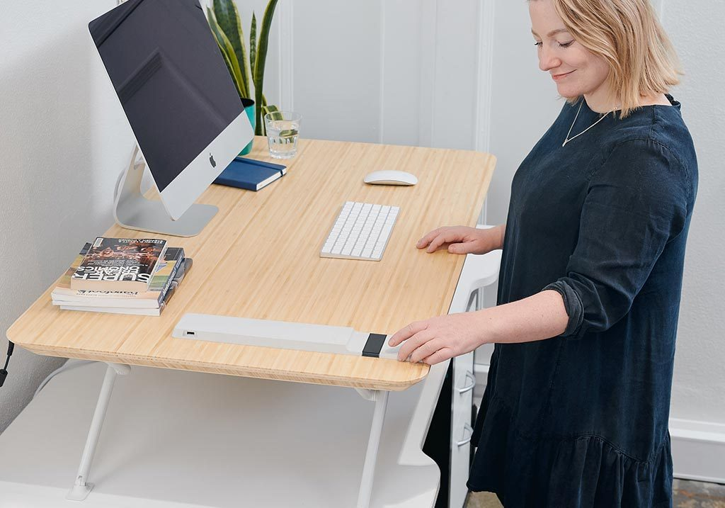White | woman adjusting standing desk