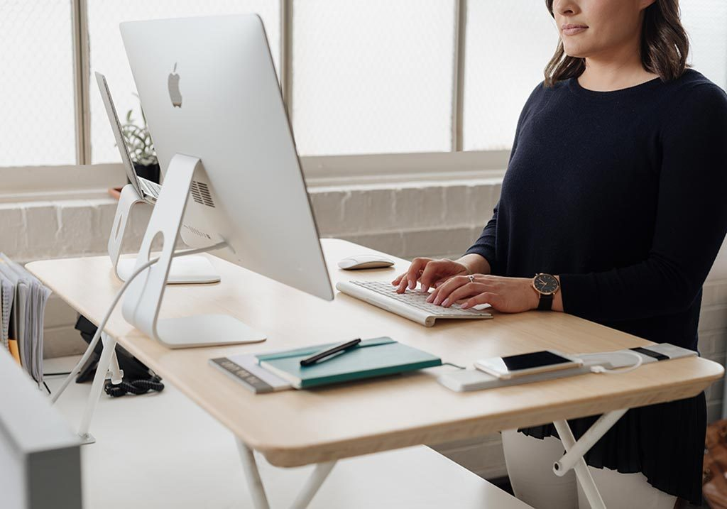 White | woman typing at standing desk