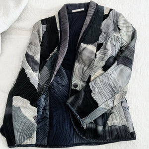 Black And Grey Quilted Jacket On Bed