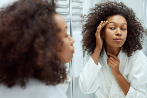 Photo of woman inspecting face in mirror
