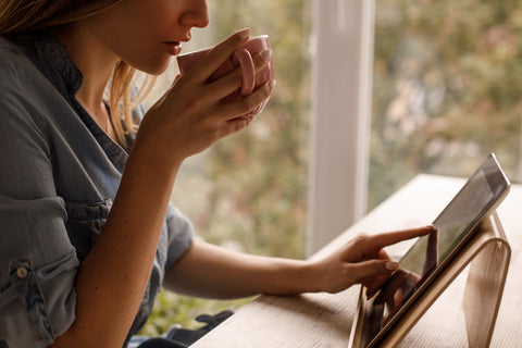 Photo of woman drinking coffee while using tablet