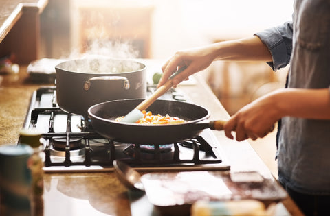 Photo of person cooking with pans