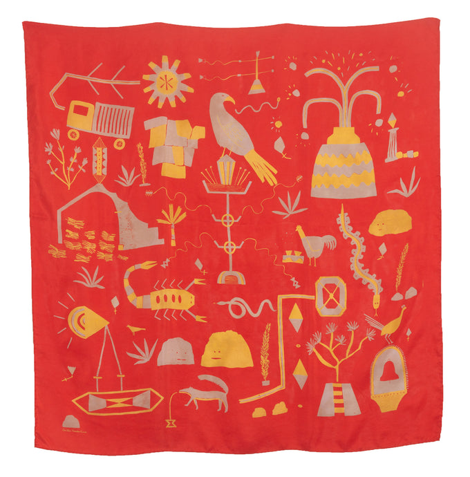 El Sueño Silk Scarf. Tomato red base colour with grey blue and yellow printed imagery. Imagery depicts animals and ruins with a volcanic landscape.