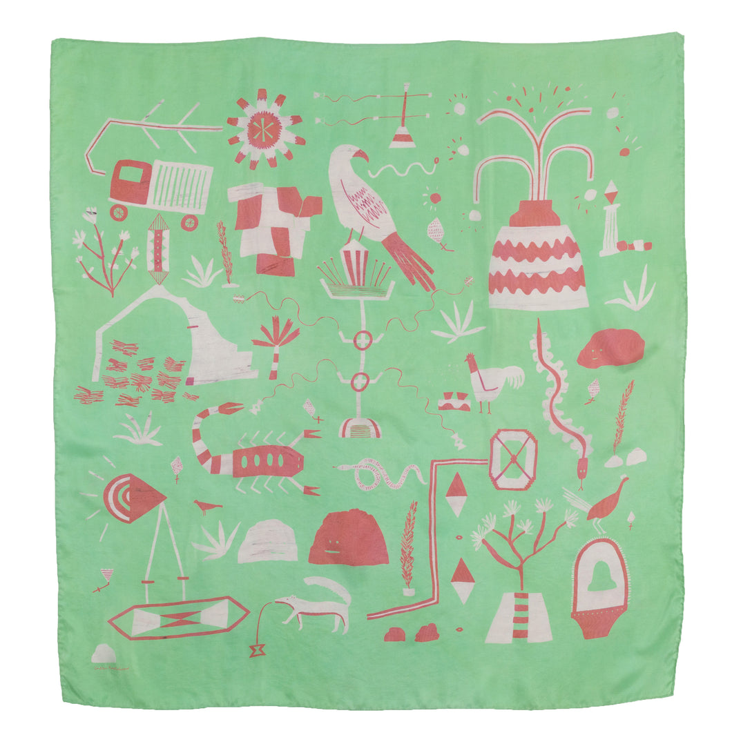 El Sueño Silk Scarf. Mint green base colour with pink and rust printed imagery. Imagery depicts animals and ruins with a volcanic landscape.