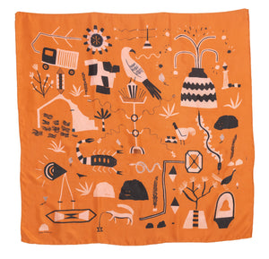 El Sueño Silk Scarf. Orange base colour with pink and navy printed imagery. Imagery depicts animals and ruins with a volcanic landscape.