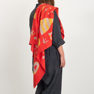 El Sueño scarf in red, draped across a model's shoulder to give a sense of drape and scale. Model is wearing a charcoal linen overall.