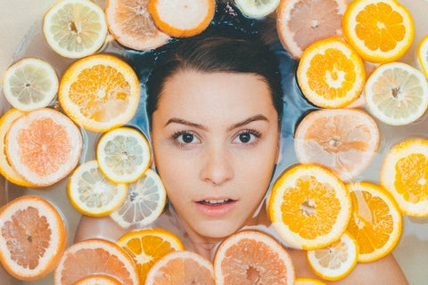 women in bath with lemons and oranges