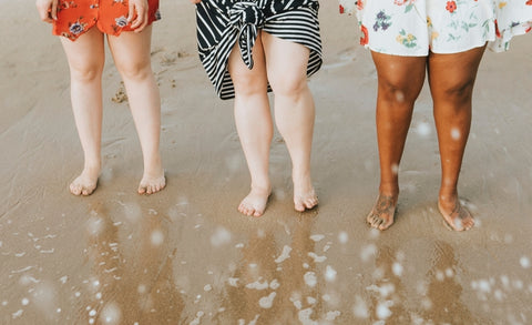 women standing on beach legs bare