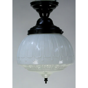 Classic milk glass globe with bronze finish fixture and finial.