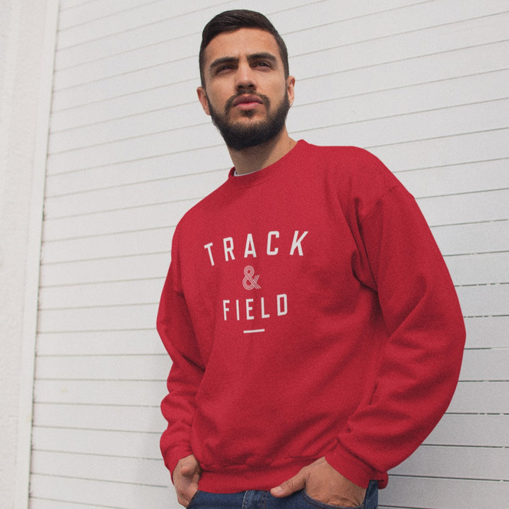 MAN LEANING ON WHITE WALL WEARING TRACK & FIELD SWEATSHIRT