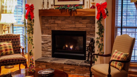 Cosy sitting room with fireplace and fireside chairs decorated for Christmas - The Sage haven