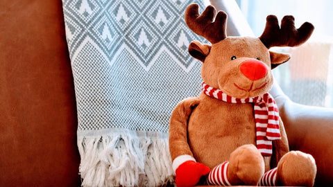 Christmas reindeer soft toy sitting on couch with Christmas blanket - The Sage haven